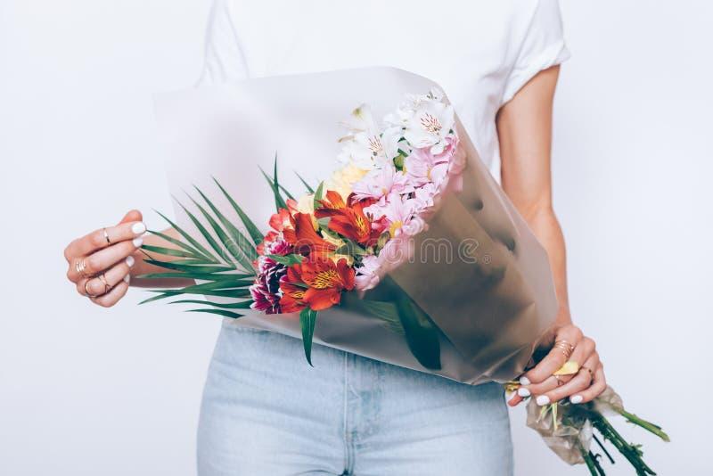 Het slanke meisje in jeans en een T-shirt houdt een boeket royalty-vrije stock fotografie