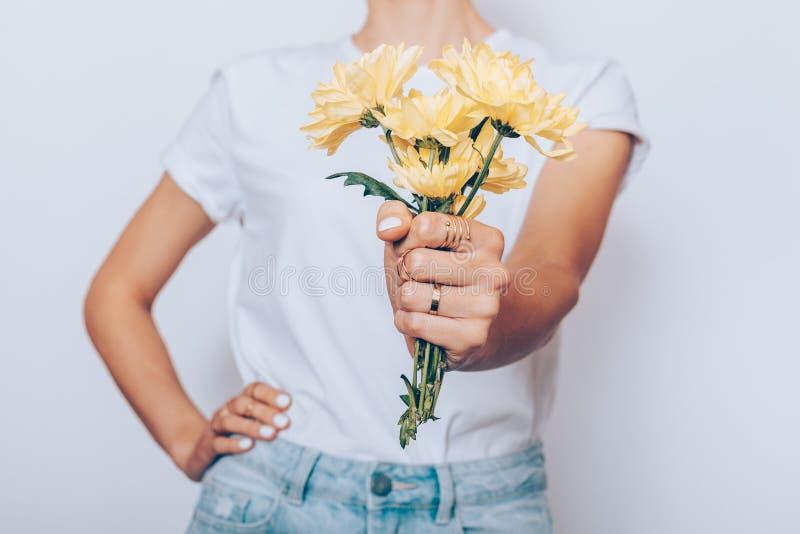 Het slanke meisje in jeans houdt een klein boeket van gele bloemen stock foto's