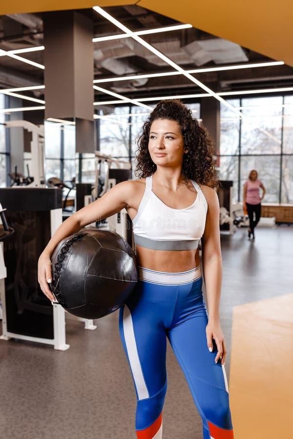 Het slanke meisje met donker krullend haar gekleed in een sportkleding bevindt zich met zware geschiktheidsbal in de moderne gymn stock foto