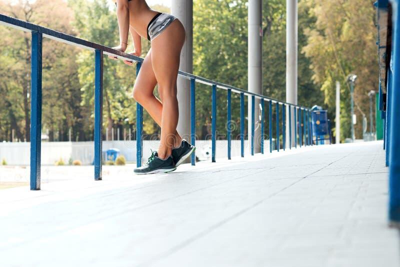 Het slanke meisje met sporten komt in korte die borrels voor, op p worden geleund stock foto