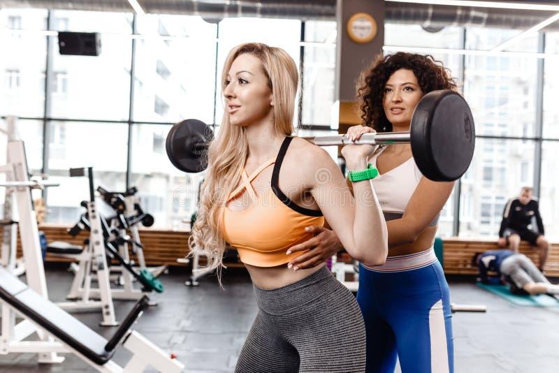 Het slanke meisje in het modieuze heldere sportenkleren doen terug hurkt met barbell en een ander atletisch meisje helpt haar in royalty-vrije stock foto's