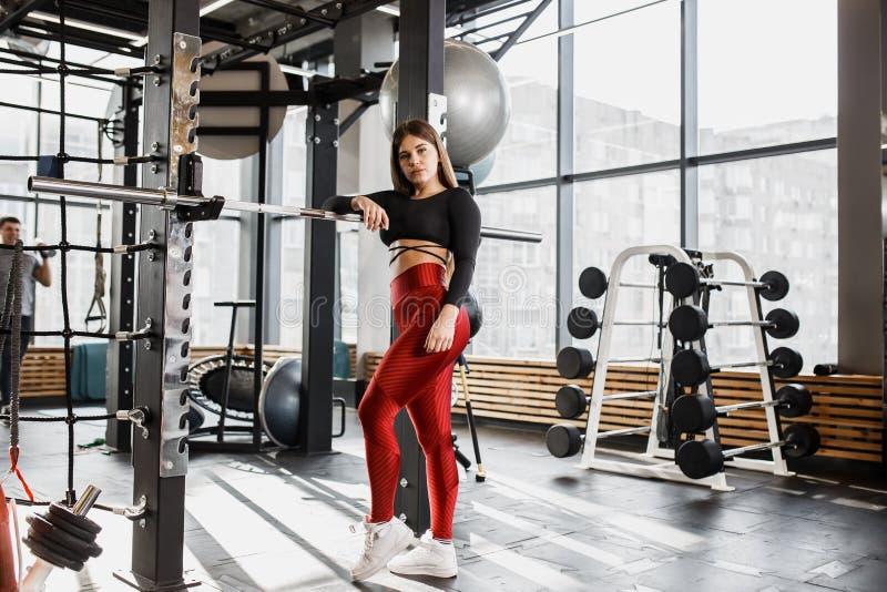 Het slanke meisje in modieuze heldere sportenkleren stelt status naast de rekstok met sport rond binnen materiaal royalty-vrije stock foto