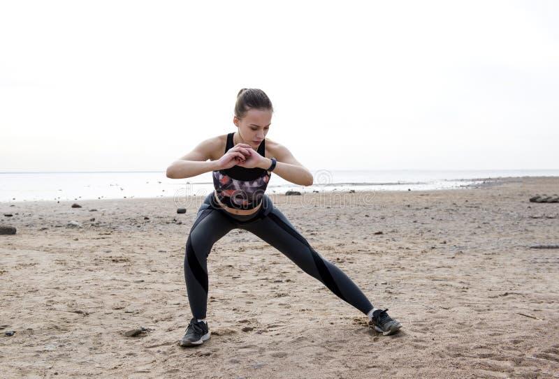 Het slanke meisje in sportenkleren is bezig geweest met sporten op het strand op het strand in bewolkt weer royalty-vrije stock afbeelding