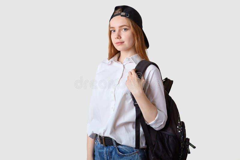 Het slanke mooie energieke schoolmeisje gaat naar school die jeans, wit overhemd, zwart GLB dragen en bagpack, kijkt geconcentree royalty-vrije stock fotografie