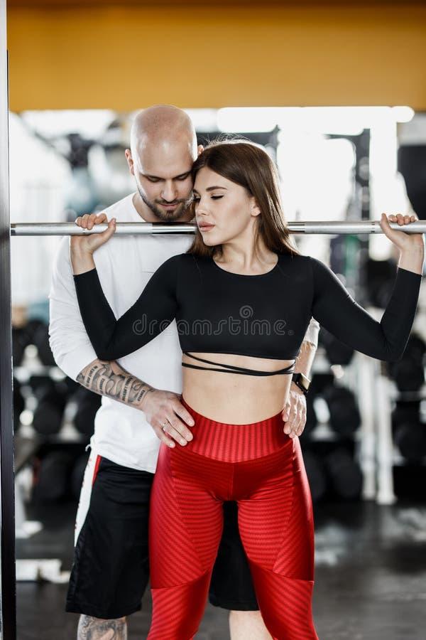Het slanke mooie meisje doet terug hurkzit en de sterke atletische mens verzekert haar in de moderne gymnastiek royalty-vrije stock afbeelding