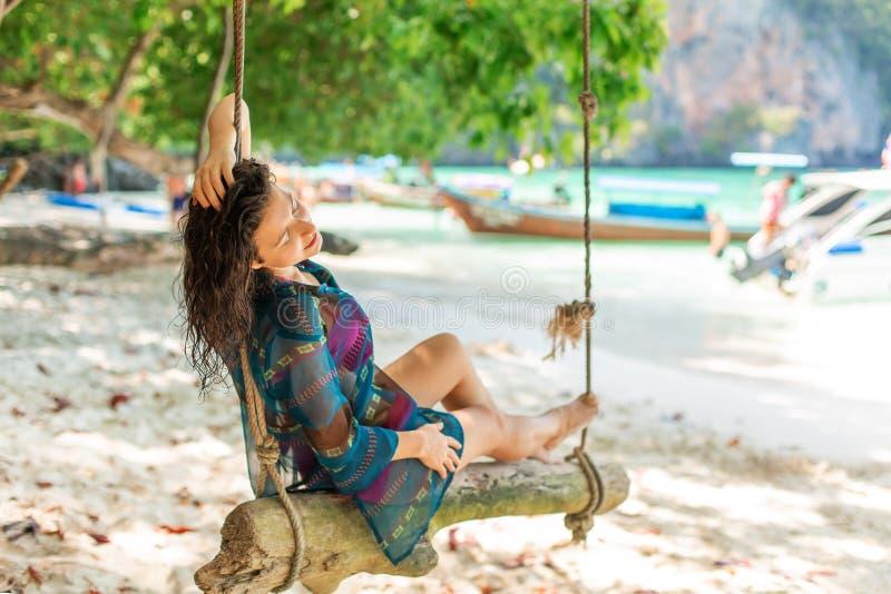 Het slanke sexy meisjesmodel in zwempak het stellen op een houten schommeling bond aan een boom Op de achtergrond van het strand  royalty-vrije stock afbeeldingen