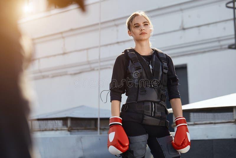 Het slanke sportieve meisje die het kostuum en de handschoenen van EMS dragen rust na opleiding royalty-vrije stock fotografie