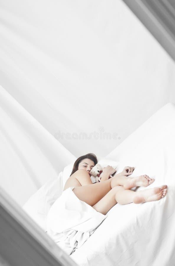 Het slapen met een teddybeer stock afbeeldingen