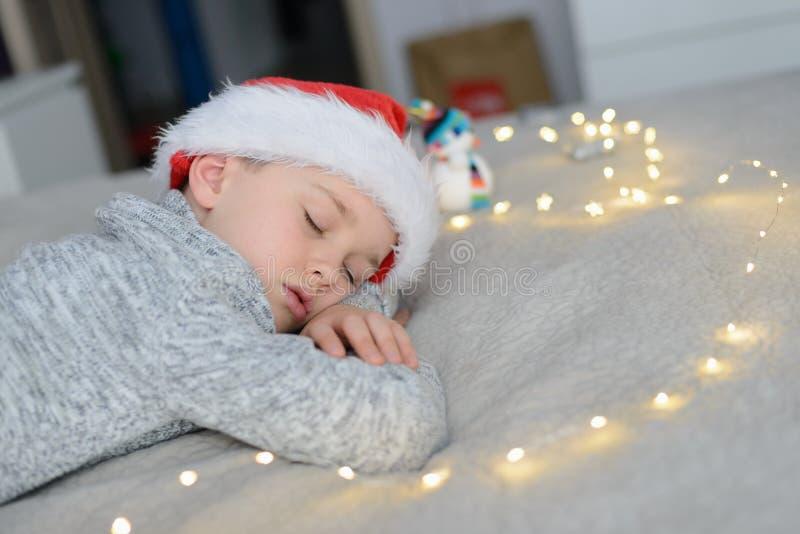 Het slapen van weinig jongenskind in Santa Claus-hoed royalty-vrije stock foto