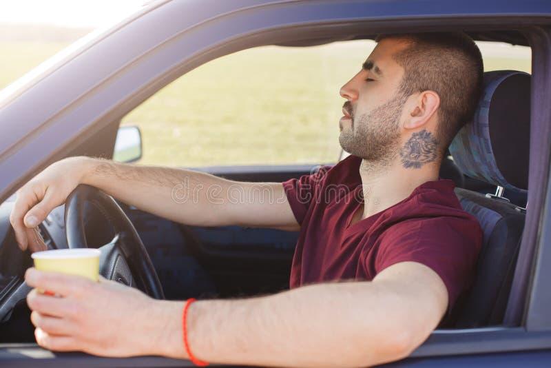 Het slaperige ongeschoren jonge mannetje zit in auto, houdt kop van koffie, voelt vermoeid zoals de aandrijvingsauto zonder rust, stock afbeeldingen
