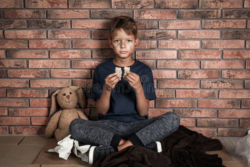 Het slechte dakloze brood van de jongensholding in handen royalty-vrije stock afbeeldingen