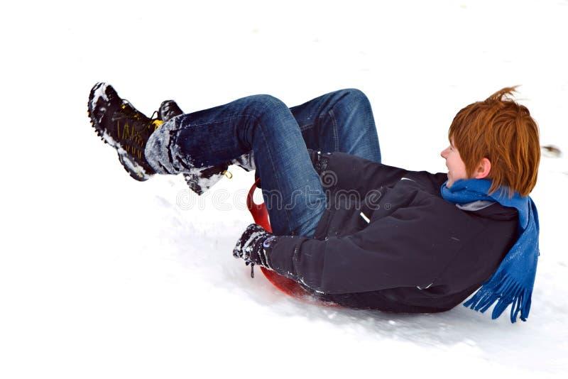 Het sledding van het kind onderaan de heuvel in sneeuw, de witte winter stock afbeeldingen
