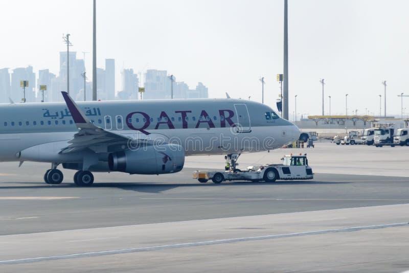 Het slepen van tractor duwend vliegtuig door de luchtvaartlijn van Qatar op de Internationale luchthaven van Doha stock foto