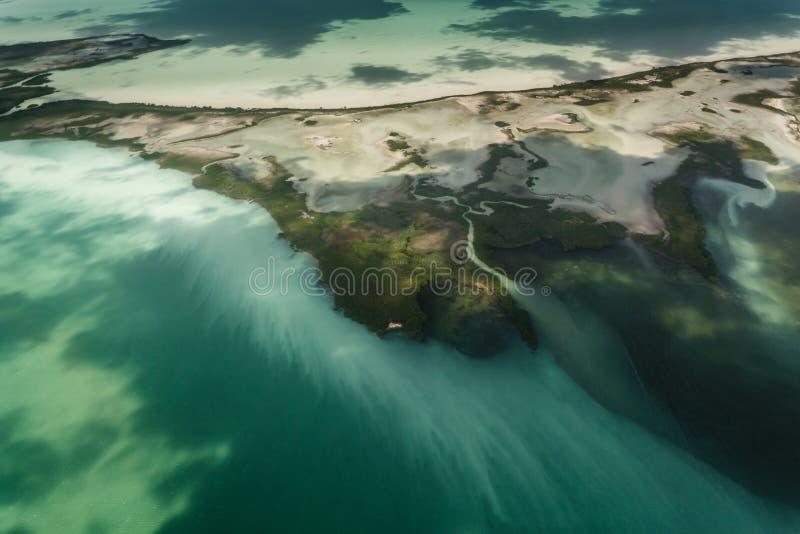 Het slib en vloeit van eiland weg verontreinigt barrièrerif stock afbeeldingen