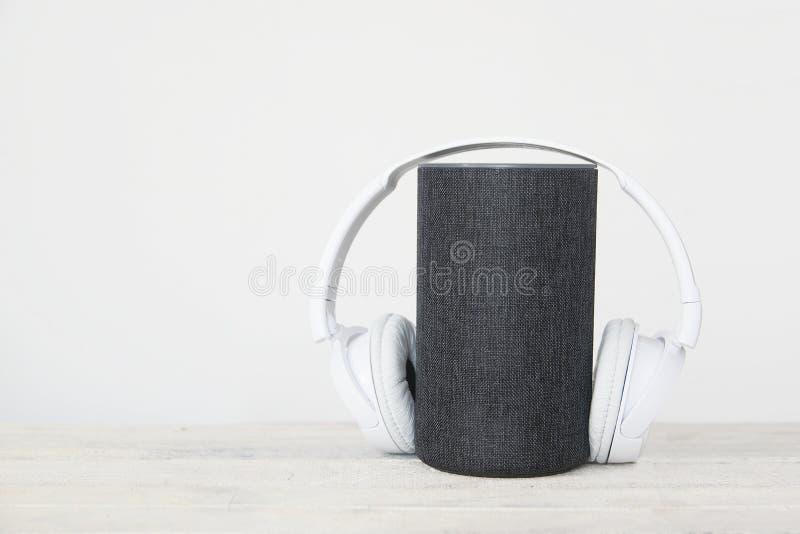 Het slimme apparaat van sprekersamazonië Alexa Echo naast sommige boeken en hearphones tegen een witte achtergrond lege exemplaar royalty-vrije stock foto