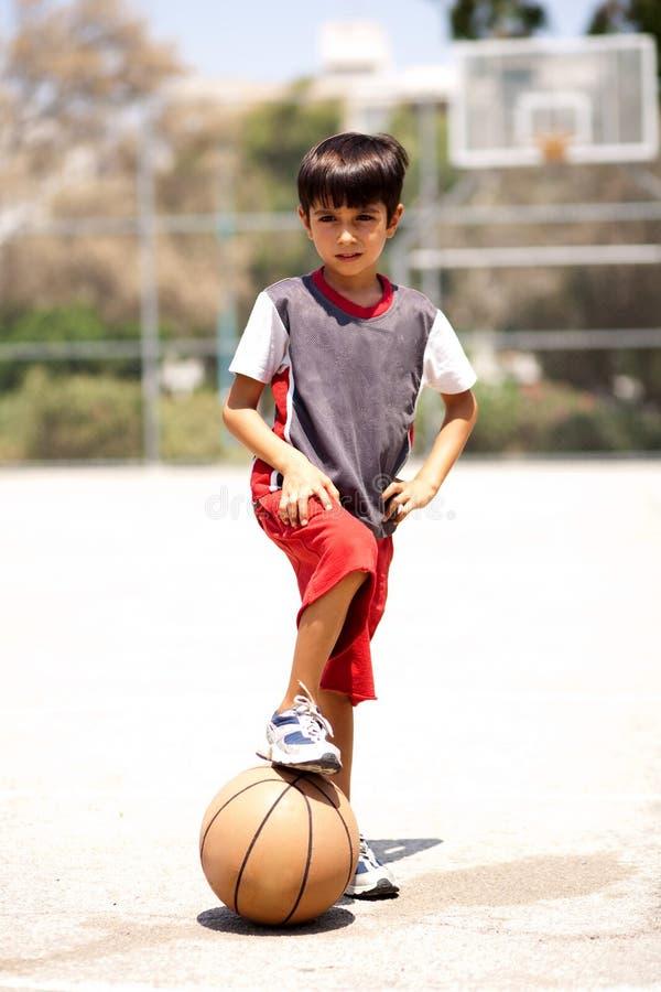 Het slimme basketbal van de jong geitjeholding onder zijn been royalty-vrije stock afbeelding