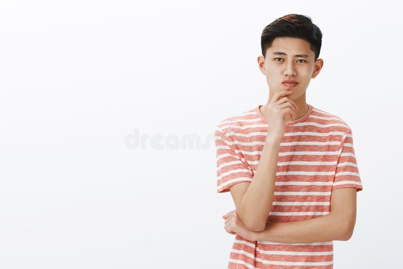 Het slimme en creatieve jonge Aziatische kerel denken aan nieuwe uitvinding Bepaalde en ambitieuze aantrekkelijke Chinese manneli stock fotografie