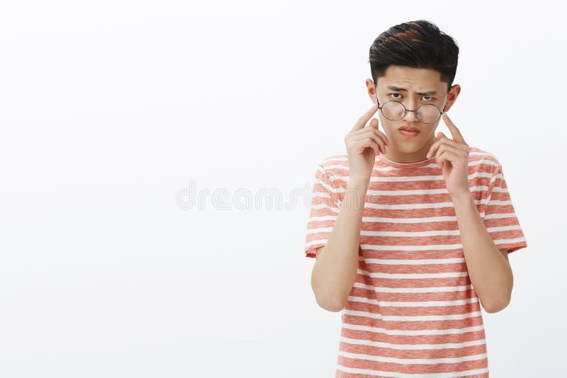 Het slimme en geconcentreerde knappe jonge mannelijke Aziatische student proberen lost taai raadsel op die glazen opstijgen, fron royalty-vrije stock foto