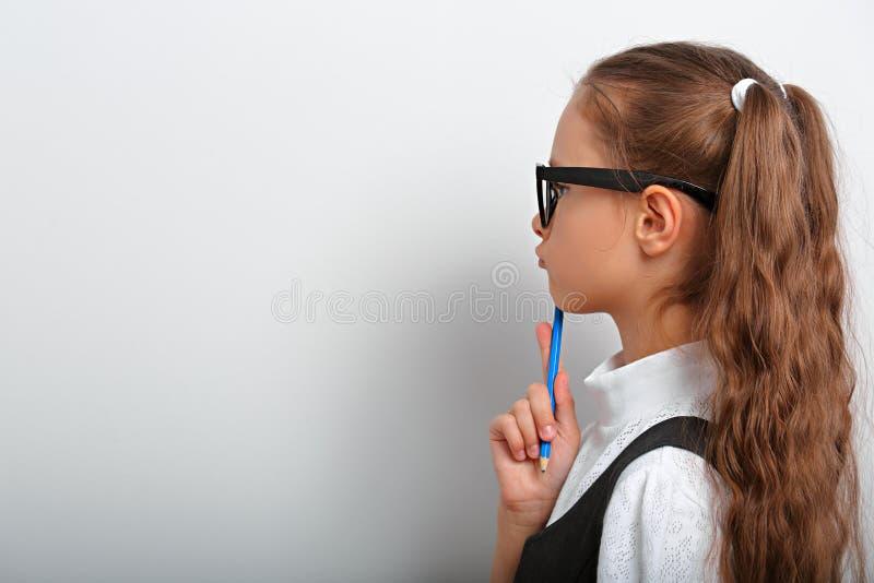 Het slimme meisje die van het leerlingsjonge geitje in oogglazen op de muurachtergrond kijken stock fotografie
