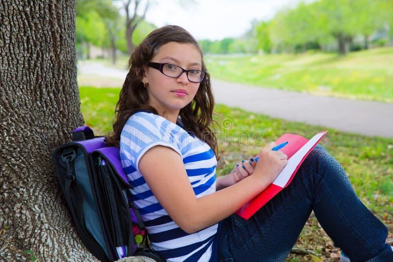Het slimme meisje van de studententiener met schooltas onder parkboom stock fotografie