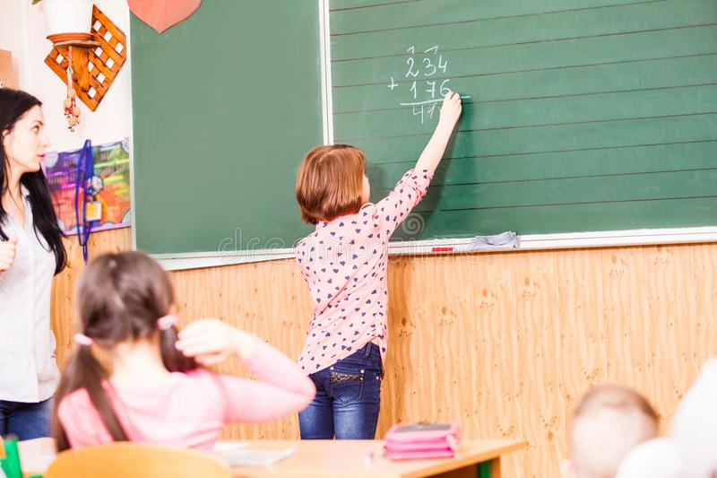 Het slimme meisje wil aan ansmer op de les stock foto