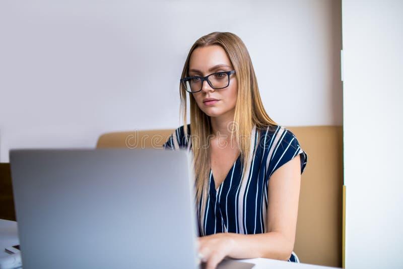 Het slimme vrouwelijke student online leren via draagbare netbook stock fotografie