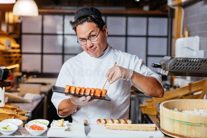 Het sluwe chef-kok wwinking aan de camera terwijl het houden van een plaat met sushi royalty-vrije stock foto