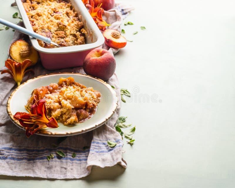 Het smakelijke dessert van de perzikkruimeltaart in plaat op lichte achtergrond met het bakken van pan en verse perziken De ruimt royalty-vrije stock foto