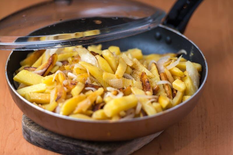 Het smakelijke huis braadde aardappels met uien, en de ketchup diende op een witte plaat royalty-vrije stock afbeelding