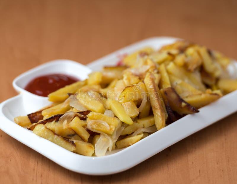 Het smakelijke huis braadde aardappels met uien, en de ketchup diende op een witte plaat stock afbeeldingen