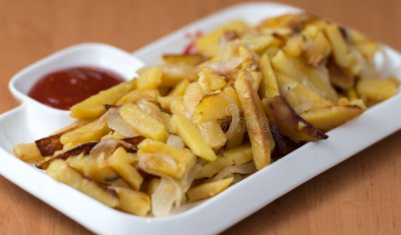 Het smakelijke huis braadde aardappels met uien, en de ketchup diende op een witte plaat royalty-vrije stock fotografie