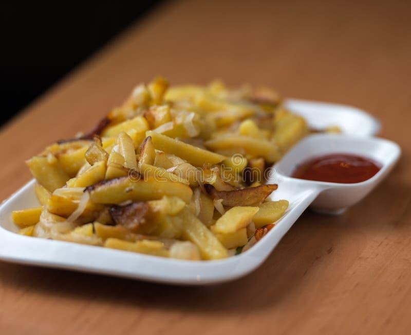 Het smakelijke huis braadde aardappels met uien, en de ketchup diende op een witte plaat stock afbeelding