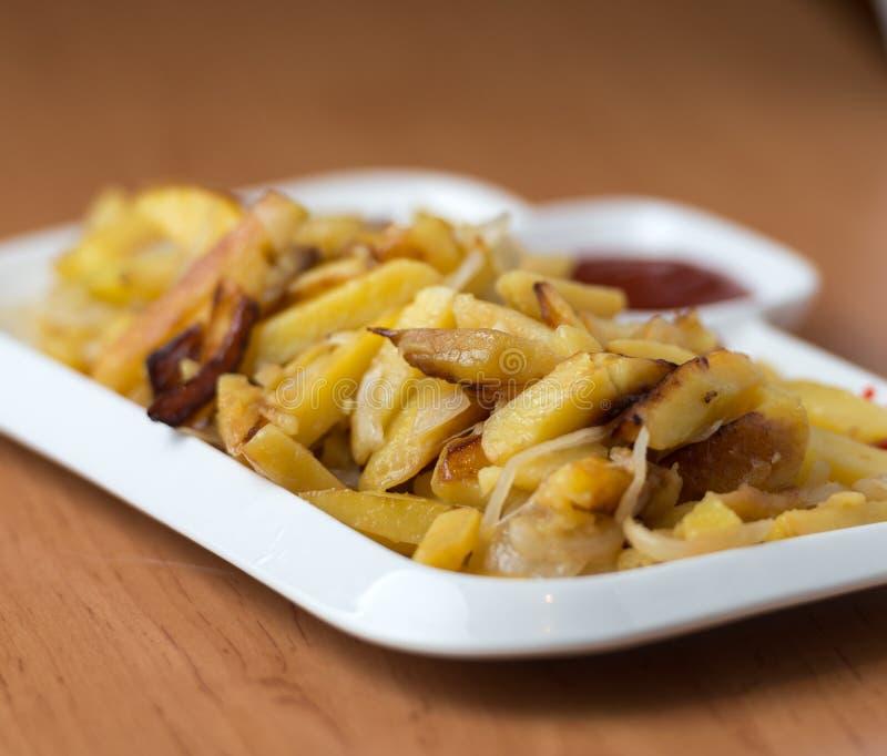 Het smakelijke huis braadde aardappels met uien, en de ketchup diende op een witte plaat royalty-vrije stock foto's