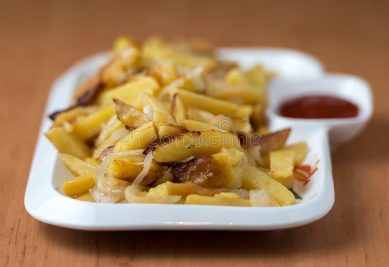 Het smakelijke huis braadde aardappels met uien, en de ketchup diende op een witte plaat stock foto