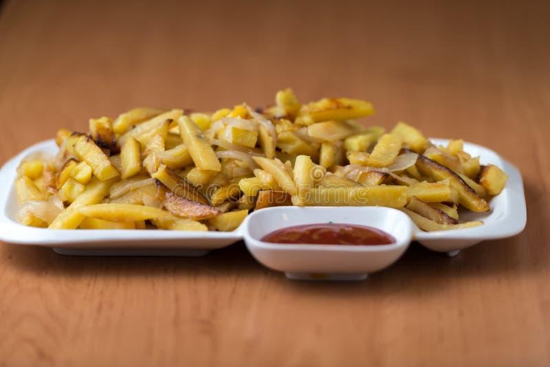 Het smakelijke huis braadde aardappels met uien, en de ketchup diende op een witte plaat stock foto's