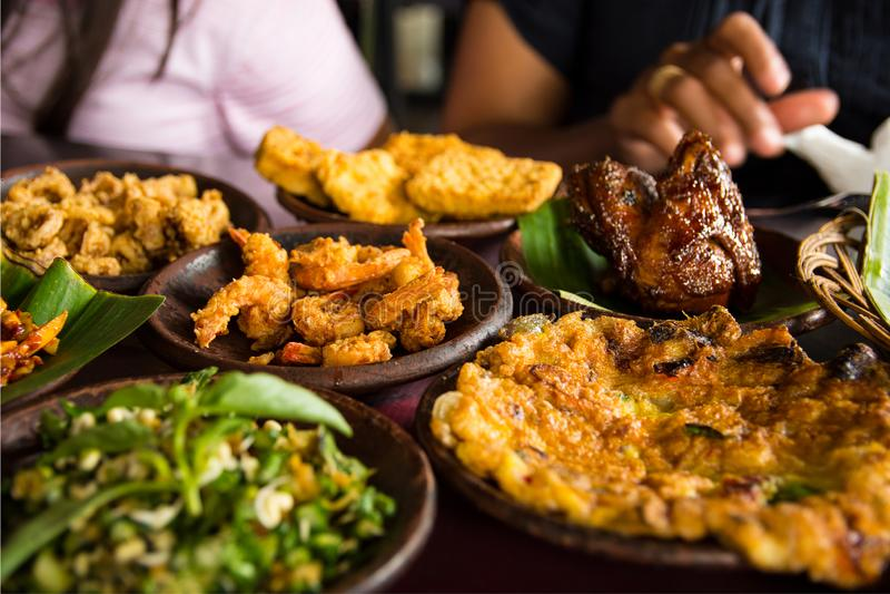 Het smakelijke kijken Indonesisch voedsel diende op de lijst met een verscheidenheid van Spaanse pepersausen, rijst, garnalen, ki stock foto