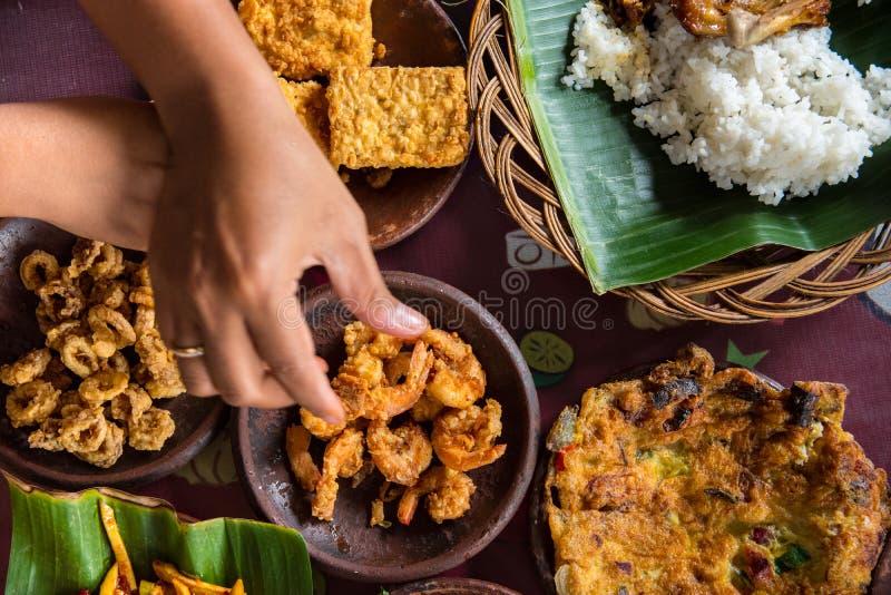 Het smakelijke kijken Indonesisch voedsel diende op de lijst met een verscheidenheid van Spaanse pepersausen, rijst, garnalen, ki stock fotografie