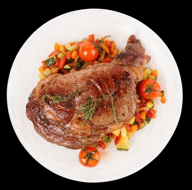 Het smakelijke ribeyelapje vlees met beweegt gebraden die groenten op zwarte worden geïsoleerd stock foto's