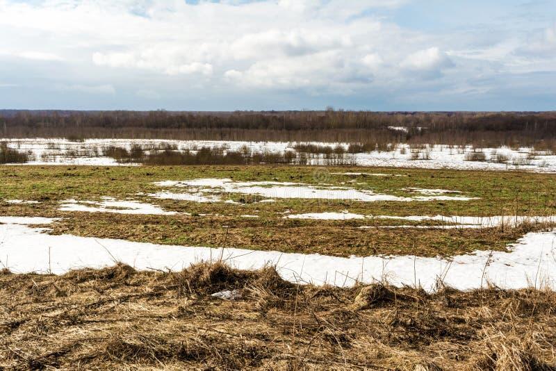 Het smelten van de sneeuw op de gebieden in de vroege lente, zonnige dag met blauwe hemel en wolken royalty-vrije stock afbeeldingen