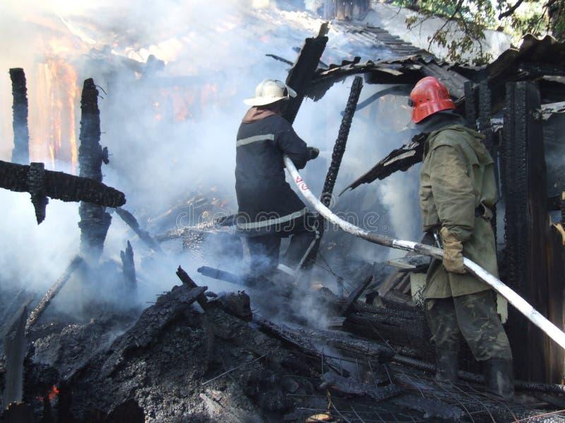 De brandbestrijders doven een brand in een flatgebouw stock foto's