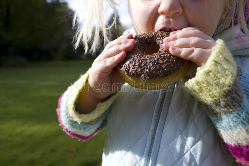 Het snacking van het kind op ongezonde chocoladedoughnut stock foto's