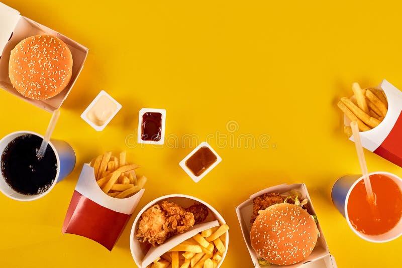 Het snel voedselconcept met vettig gebraden restaurant neemt als uiringen, hamburger, gebraden kip en frieten als a stock fotografie