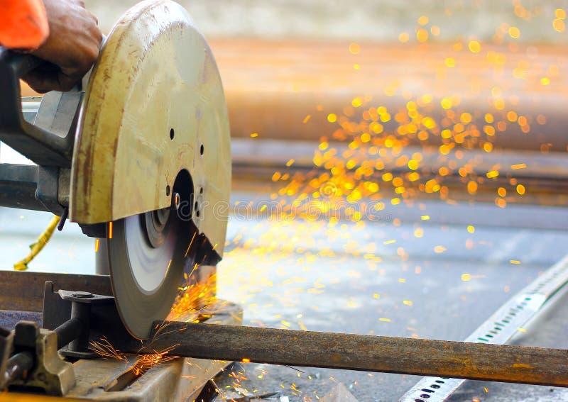 Het snijden van de bars van het ijzerstaal TMT met gemotoriseerde staalsnijder en generatie van vonken stock afbeelding