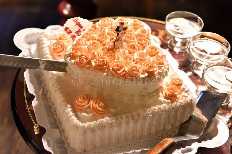 Het snijden van de huwelijkscake met champagne voor gasten stock afbeelding