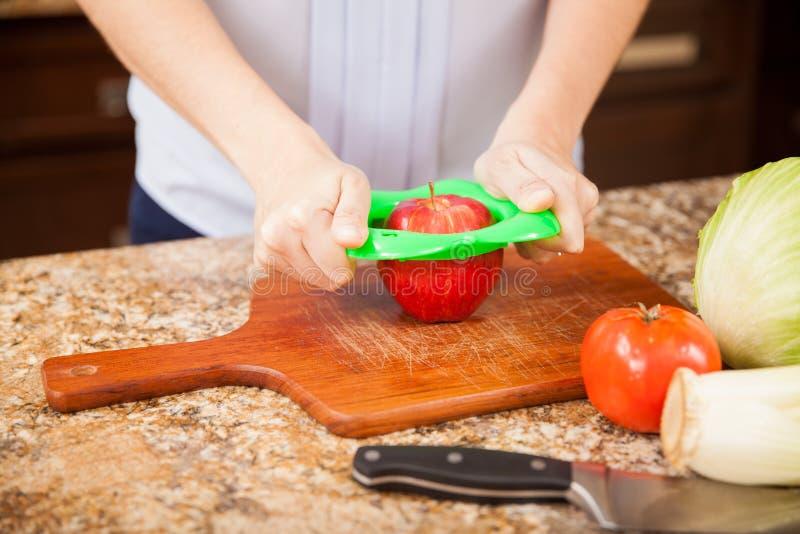 Het snijden van een appel in de keuken stock fotografie