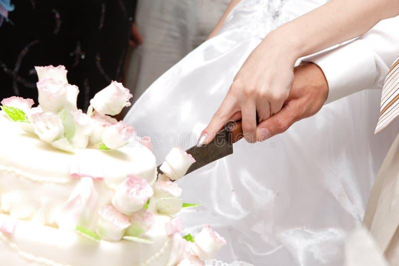 Het snijden van een huwelijkscake stock foto's