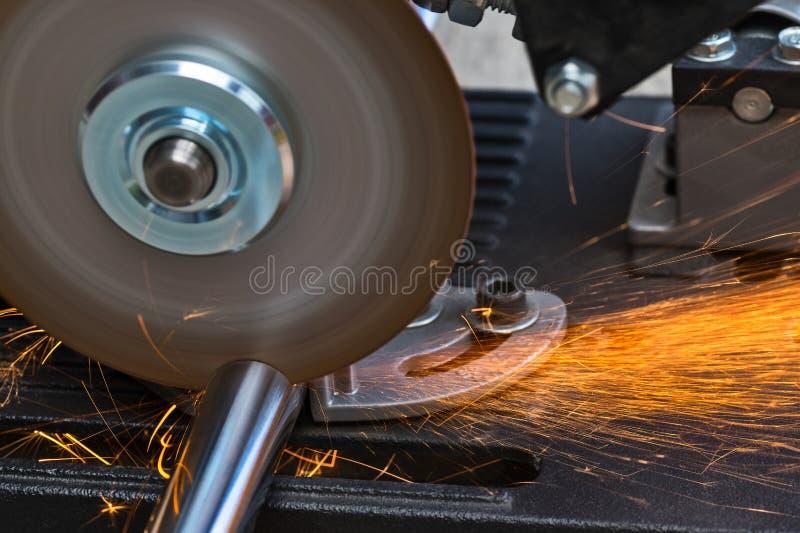 Het snijden van een metaalstaaf door een cirkelzaagmachine stock foto