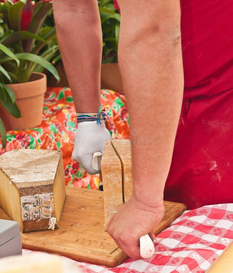Het snijden van een plak van Franse kaas stock afbeeldingen