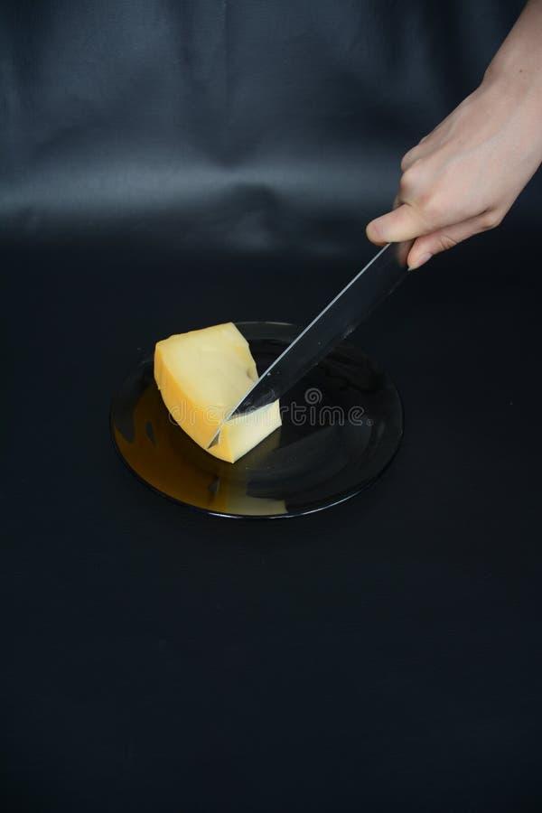 Het snijden van een plak van Schweitzer-kaas op een glasplaat royalty-vrije stock foto