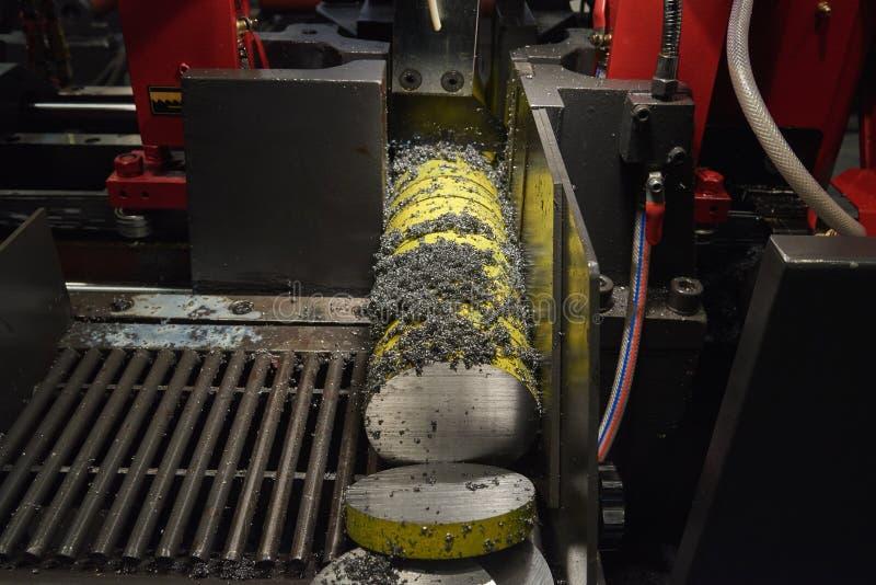 Het snijden van een ronde metaalbar met een lintzaag Spaanders en dalingen van olievlieg uit het scherpe gebied stock afbeelding